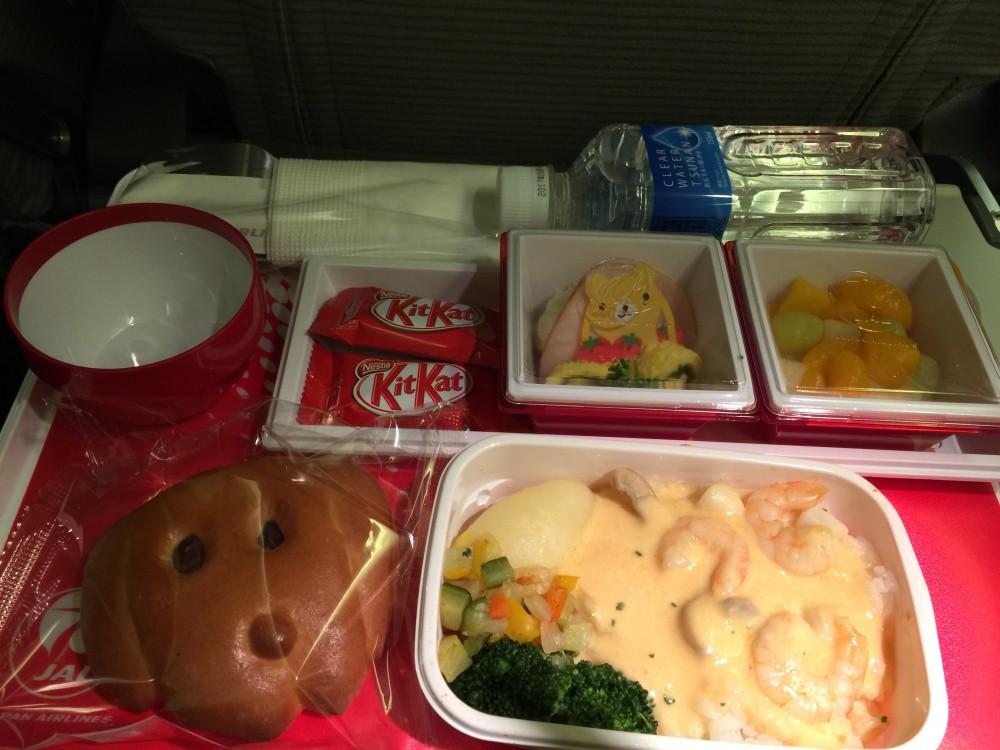 行きの飛行機のキッズミール。夕食。クリームドリアとサラダ2種。おやつは菓子パンとキットカット。