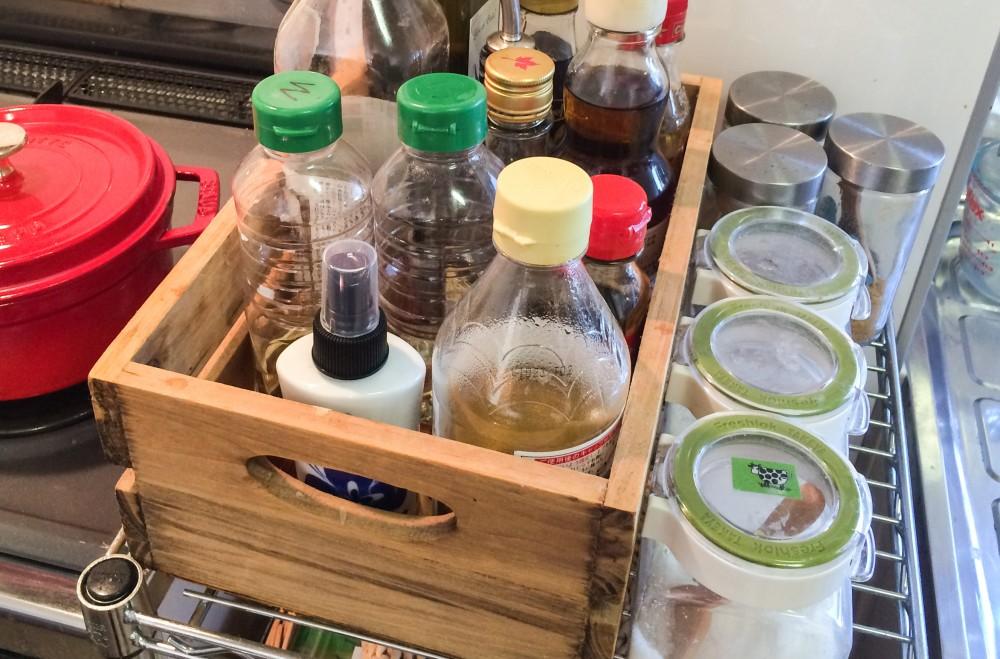 液体調味料は木箱に入れてすっきり、粉末調味料は容器をそろえ統一感を。